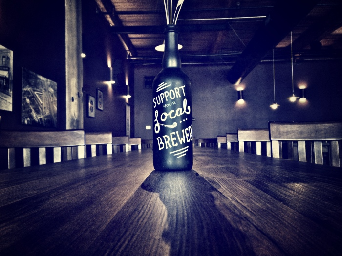 Decorated bottles at Rohrbach's Railroad St. Brewery remind patrons to Drink Local.